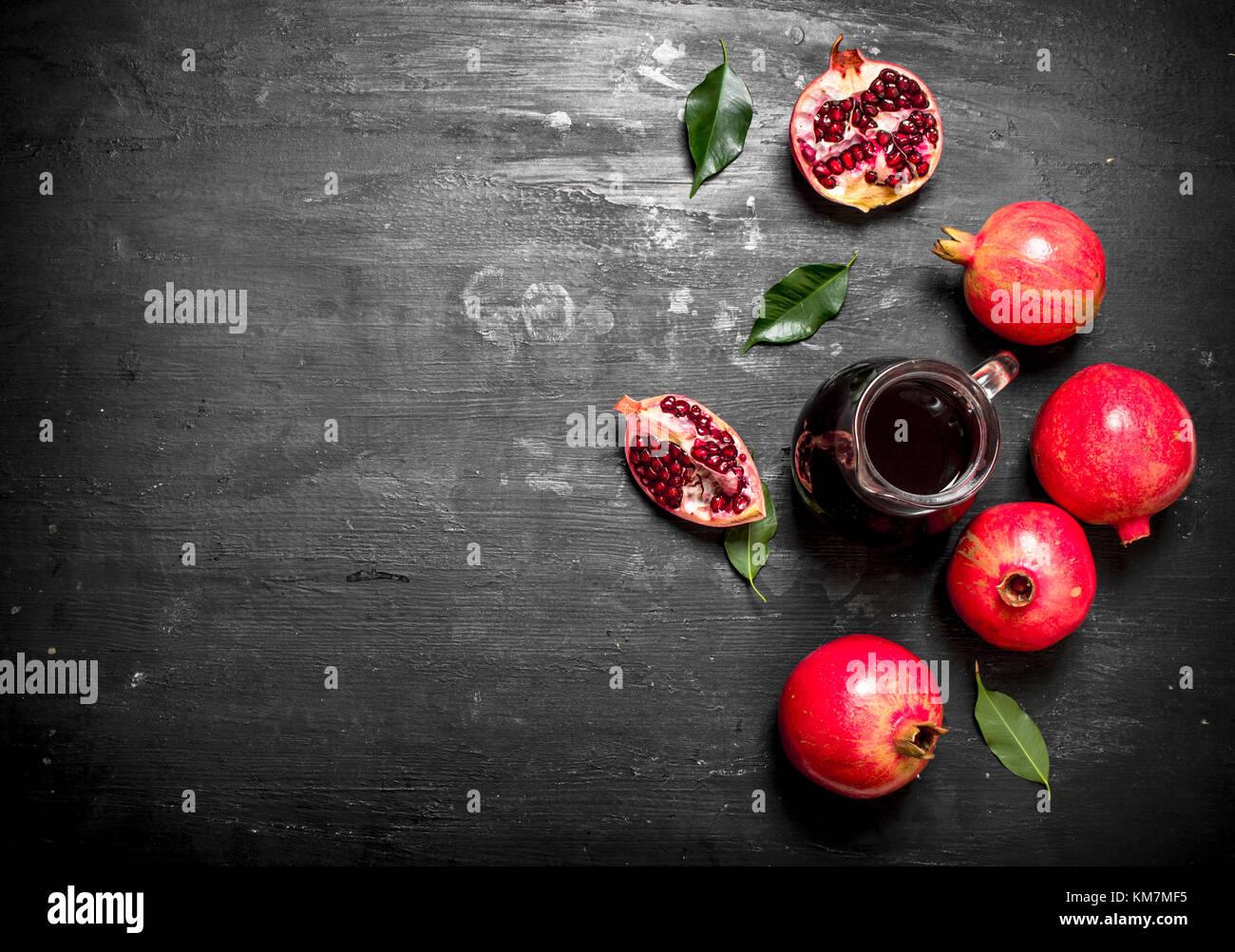 The fresh juice of ripe pomegranate. The black chalckboard. - Stock Image
