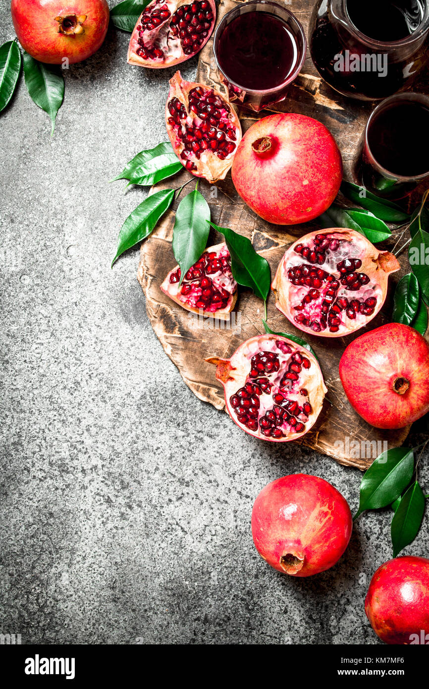 The juice of ripe pomegranate. On rustic background. - Stock Image