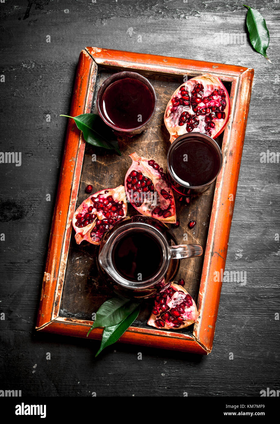 The fresh juice of ripe pomegranate. The black chalckboard. Stock Photo