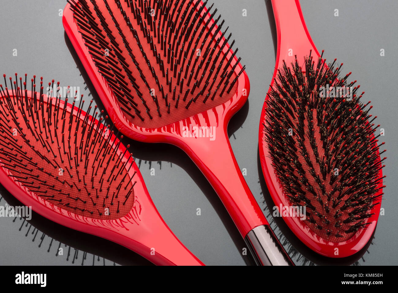 Three Red Hair Brushes - Stock Image