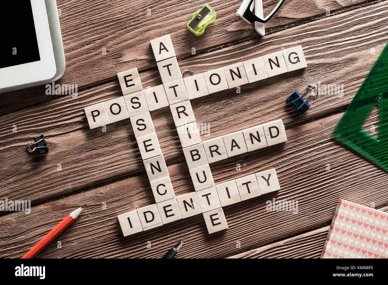 Conceptual business keywords on table with elements of game making crossword - Stock Image