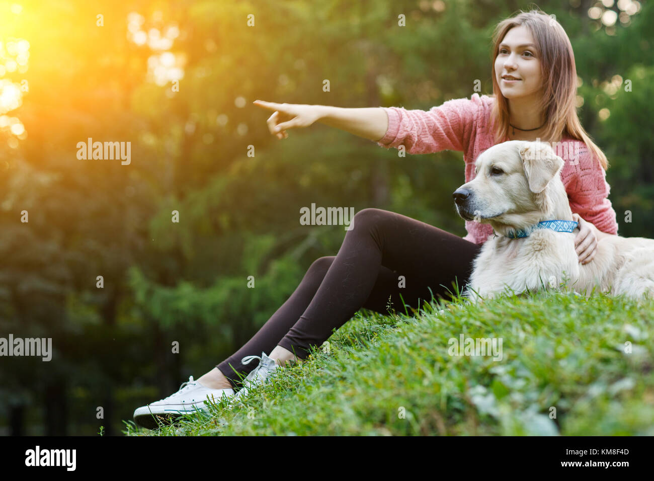 Photo of girl pointing forward next to dog on green lawn - Stock Image