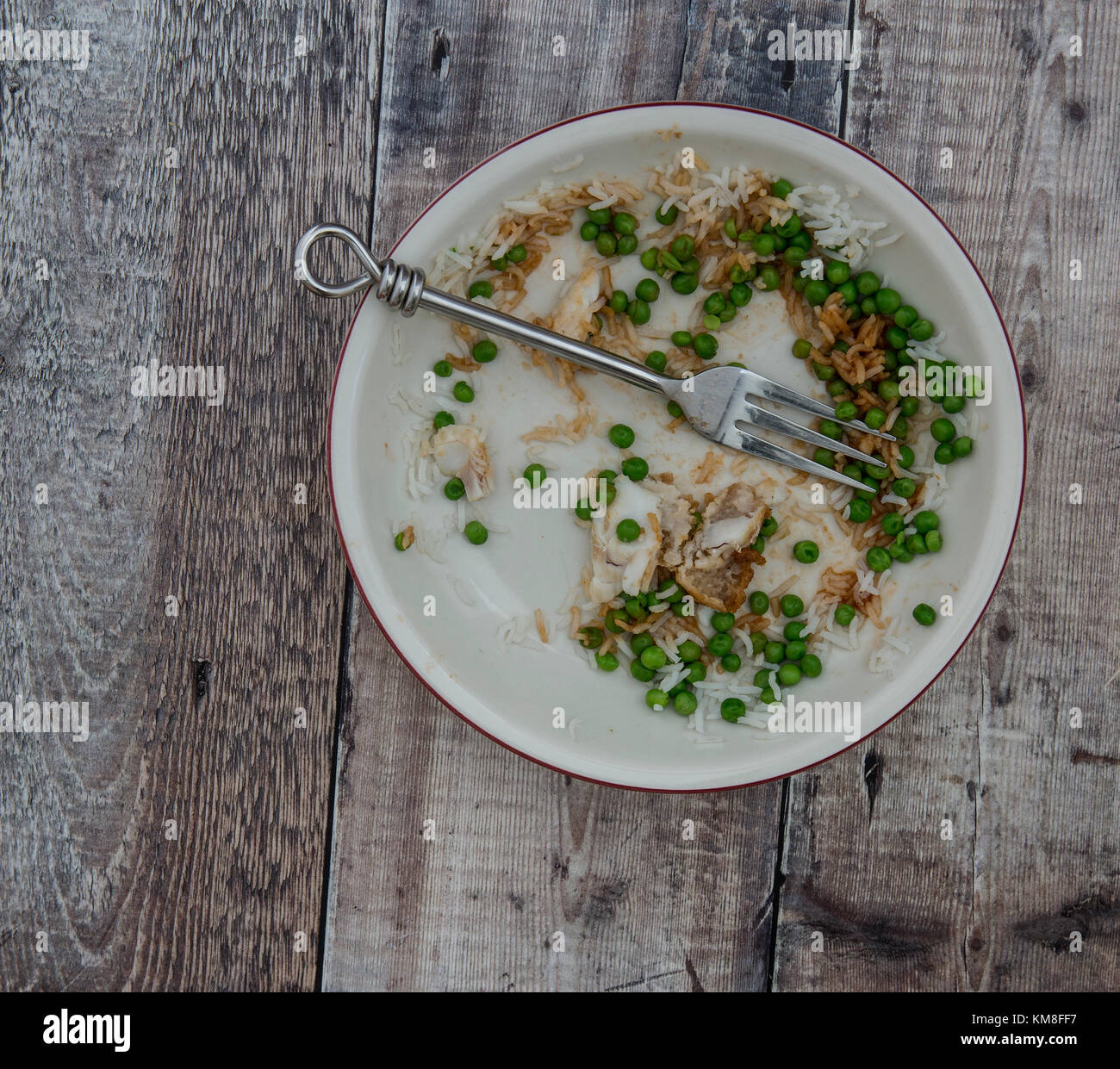 Dish of leftovers on a rustic wooden background with copy space - Stock Image