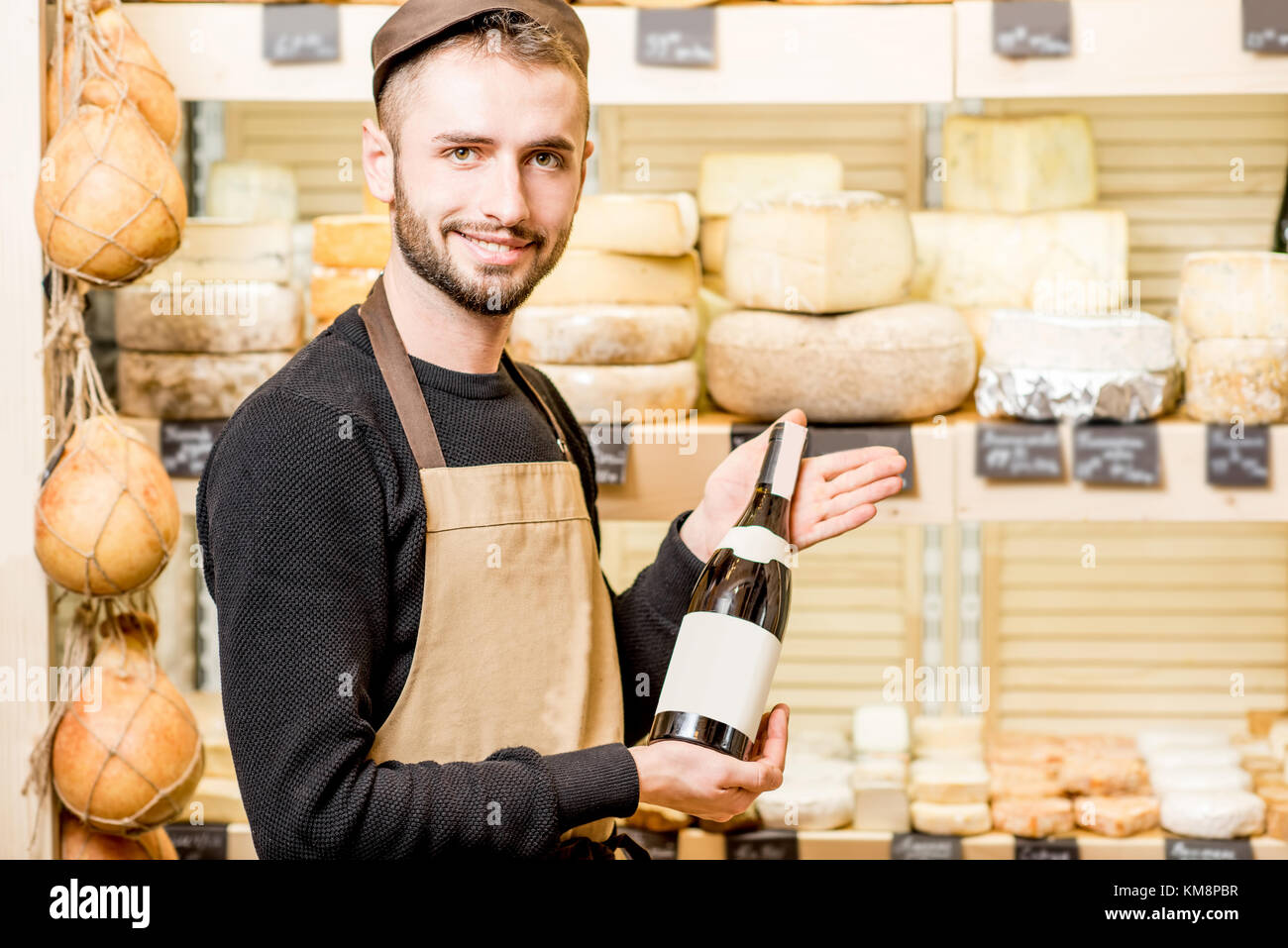Portrait of a young sommelier in uniform standing with wine bottle