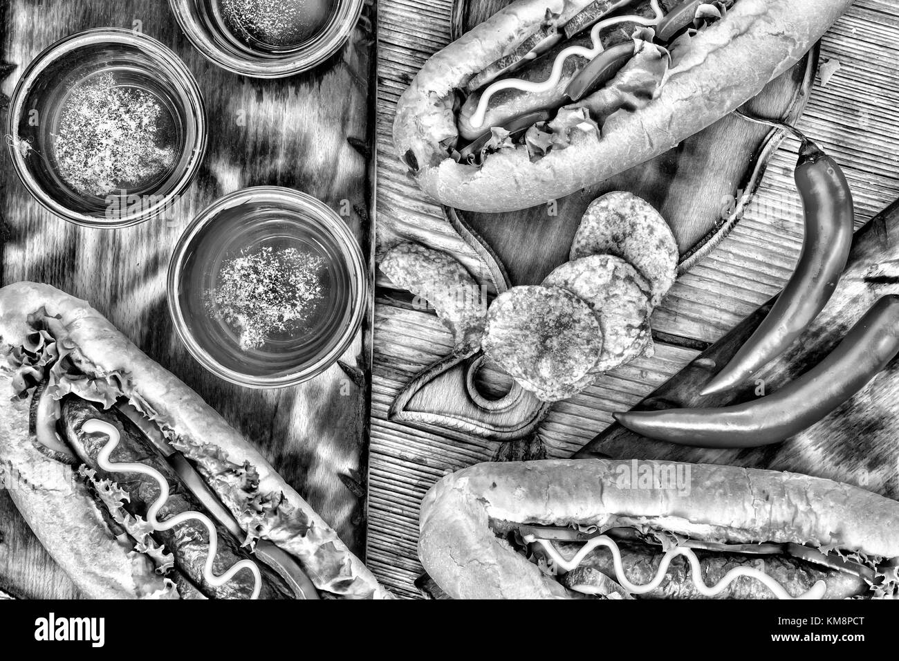 Black and white photo. Hot dogs, beer, chips on wooden table in the pub. - Stock Image