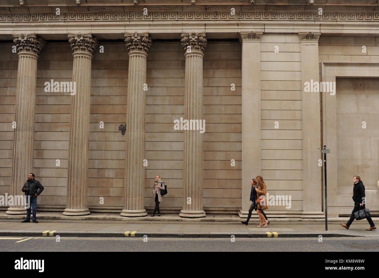 People walk past The Bank of England in London - Stock Image