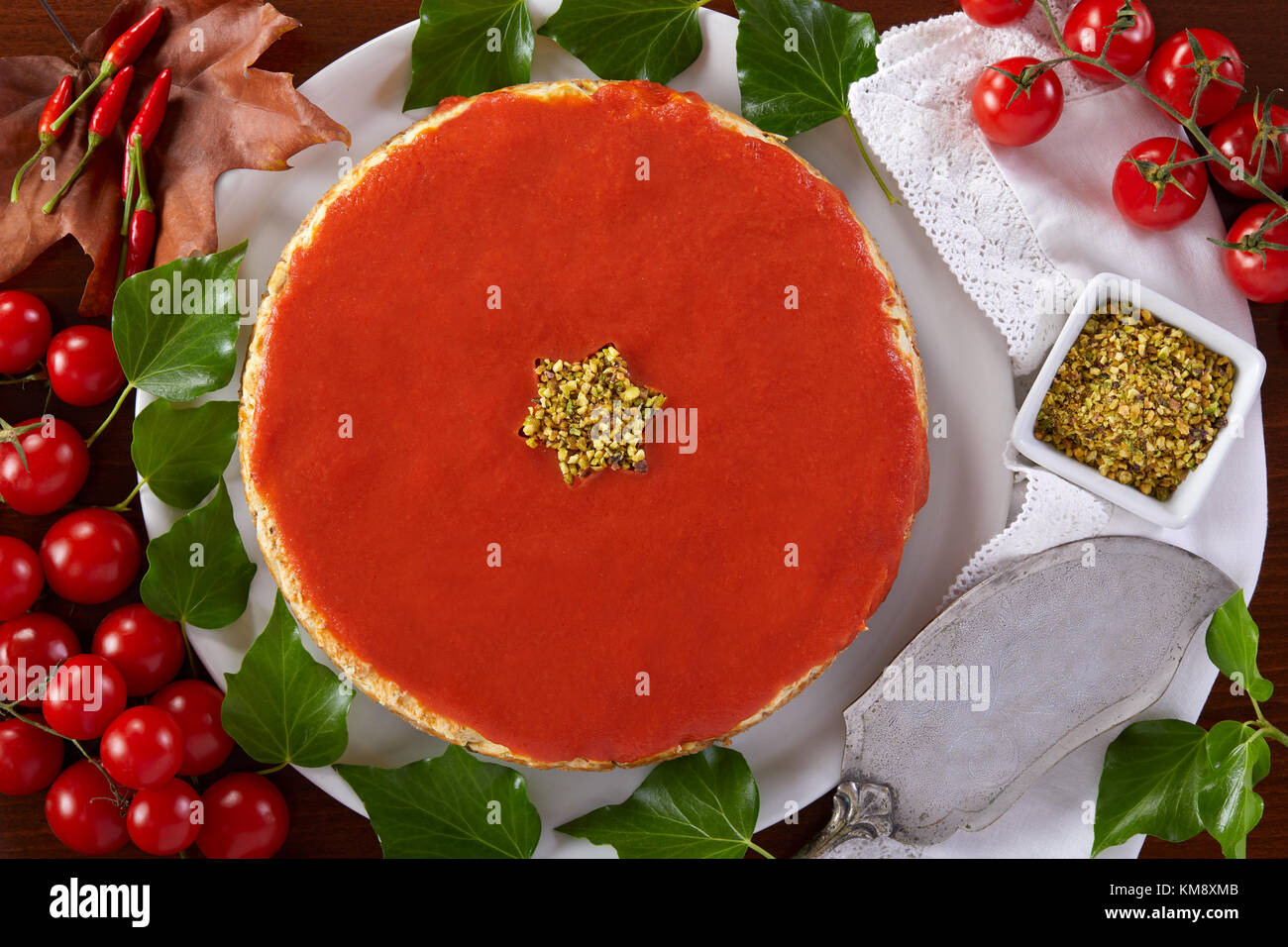Savory cheesecake for Christmas prepared with cheese, zucchini, pistachios and tomato sauce. - Stock Image
