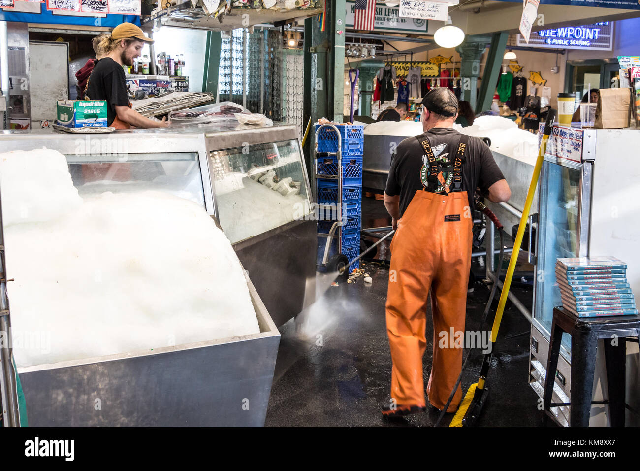 Seattle, Washington, USA - September 4th, 2017: Male worker wearing a waterproof fishing pants is cleaning the floor - Stock Image