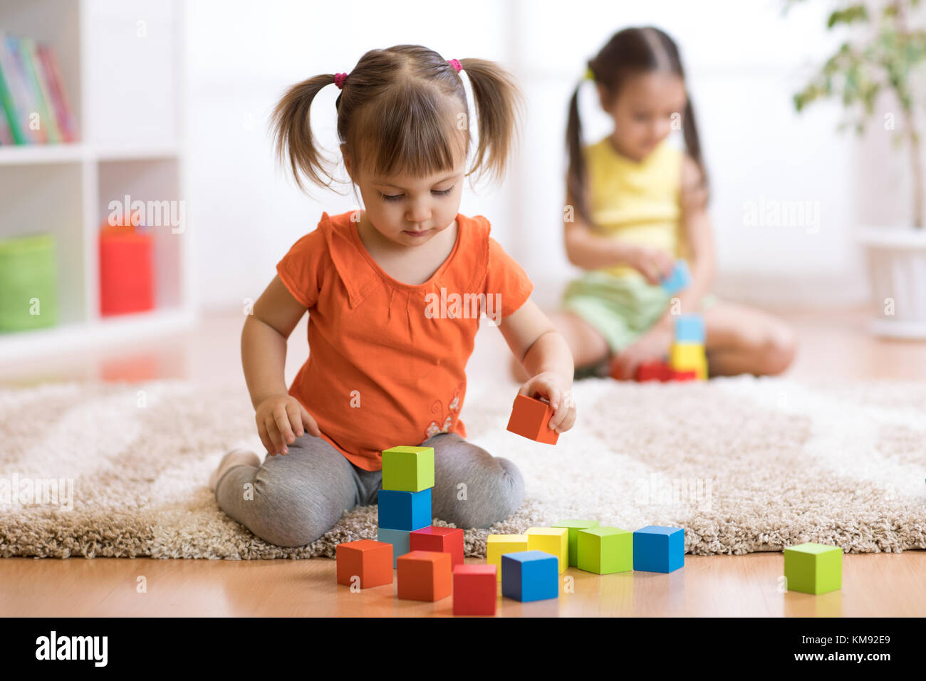 Children toddlers girls playing toys at home, kindergarten or nursery - Stock Image