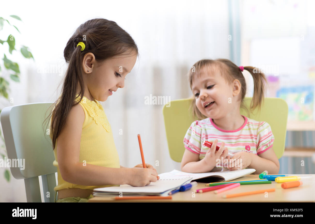 Kids drawing in kindergaten. Children painting in nursery. Preschooler with pen at home. Creative toddlers. Stock Photo
