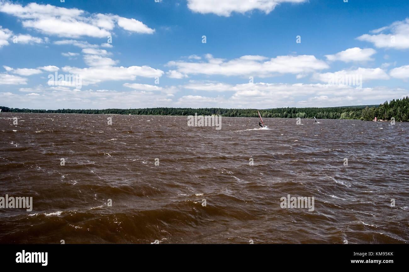 windy Velke Darko pond with wavesm sailboats and blue sky with clouds on Ceskomoravska vrchovina near Zdar nad Sazavou Stock Photo