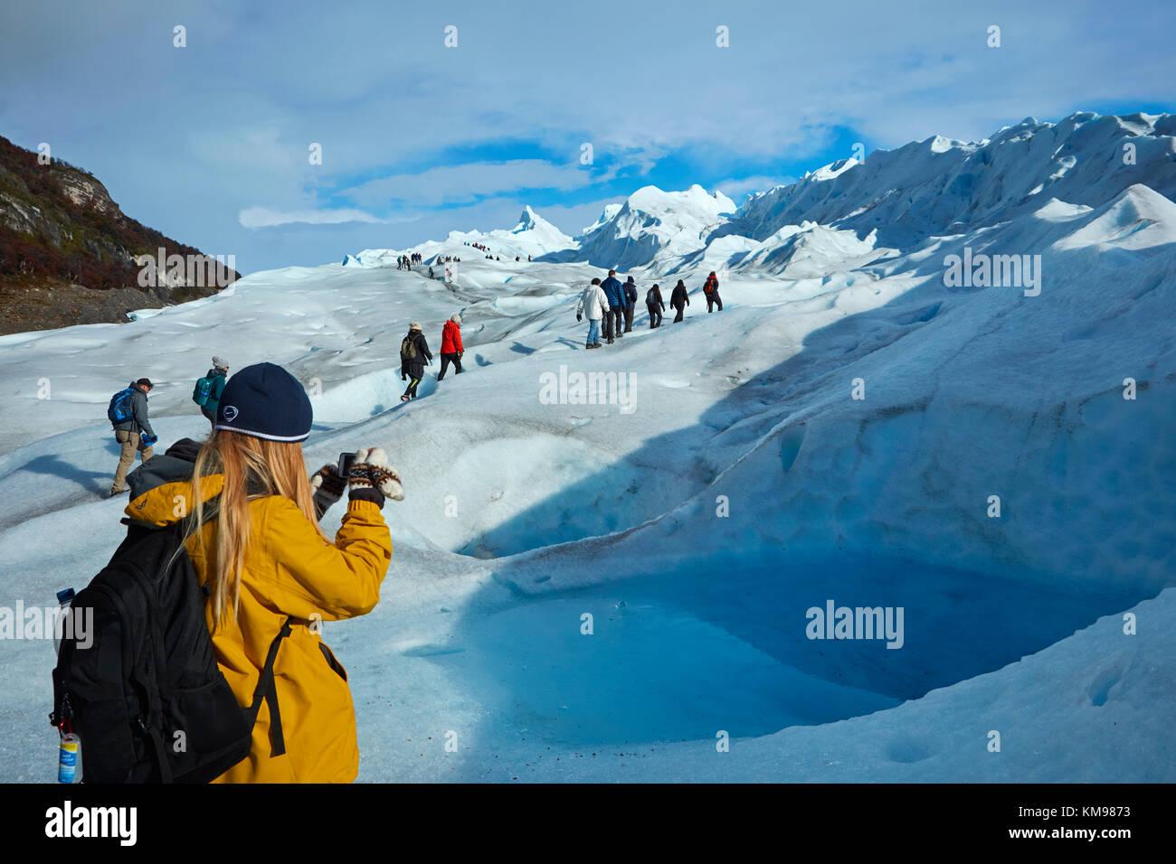 Tourist photographing blue pool on Perito Moreno Glacier, Parque Nacional Los Glaciares (World Heritage Area), Patagonia, Stock Photo