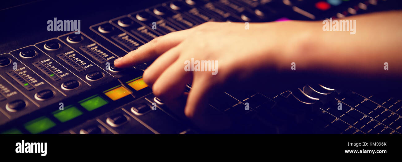 Cropped hand of woman using sound mixer at recording studi Stock Photo