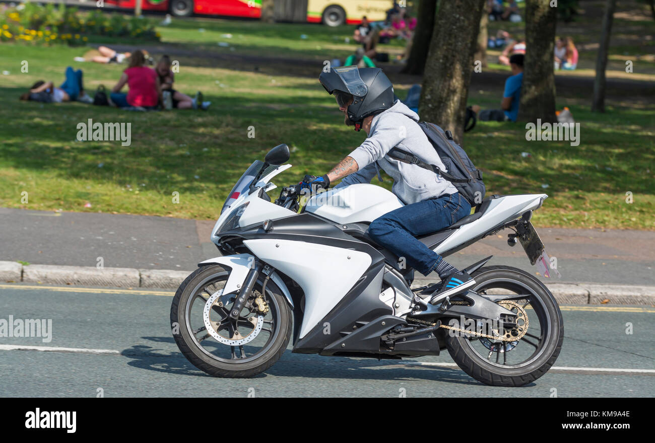Man riding a motorbike without wearing any protective clothing other than a crash helmet, in the UK. - Stock Image