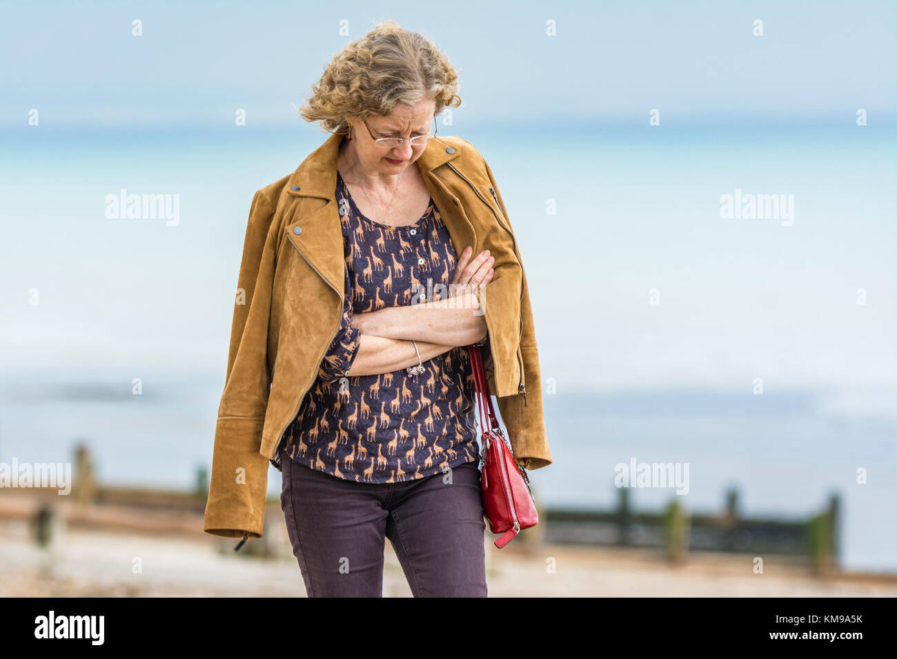 Woman walking with her arms folded, looking deep in thought and in a world of her own. - Stock Image