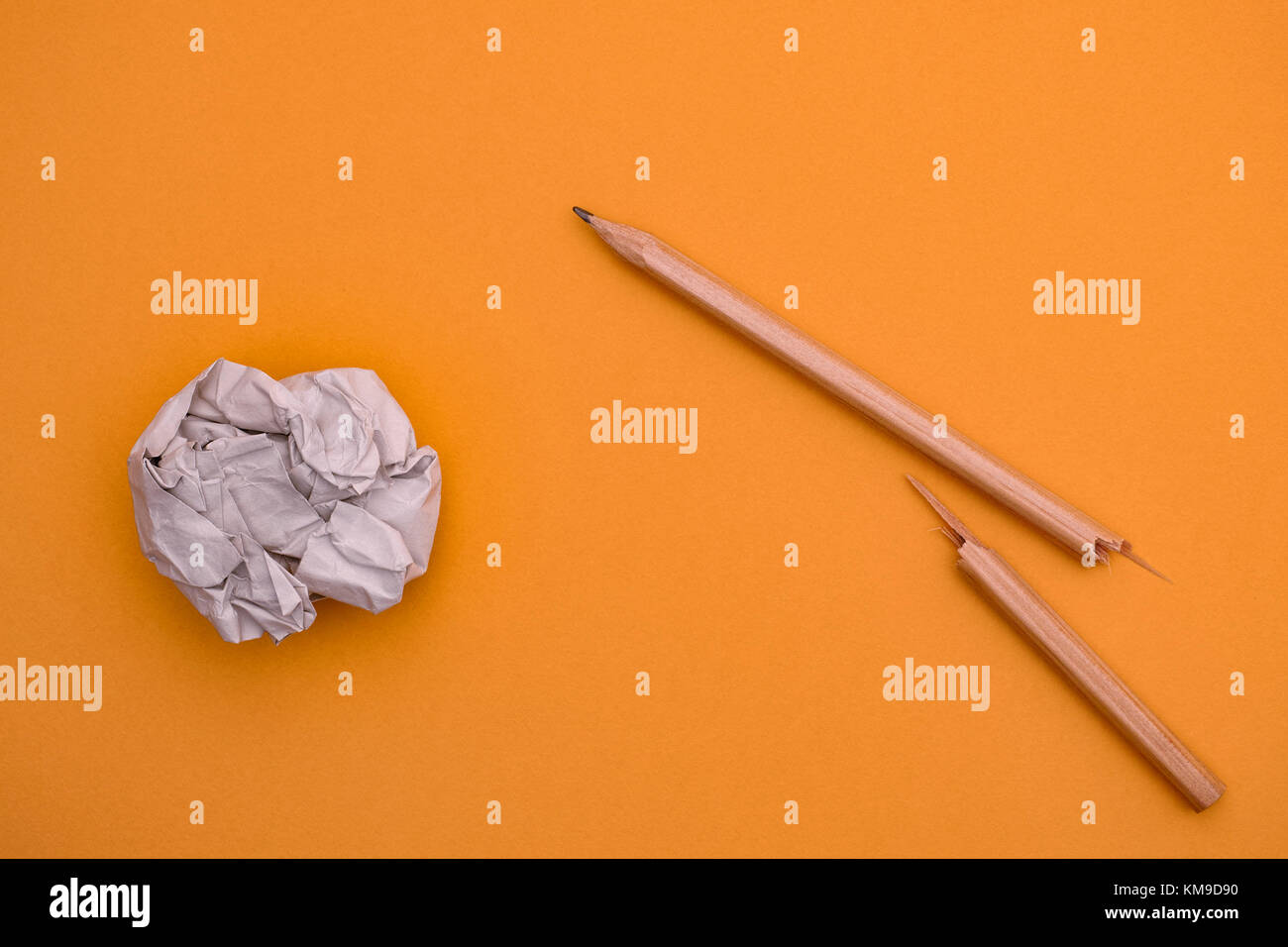Broken pencil and crumpled paper ball on a yellow background. Close up. - Stock Image