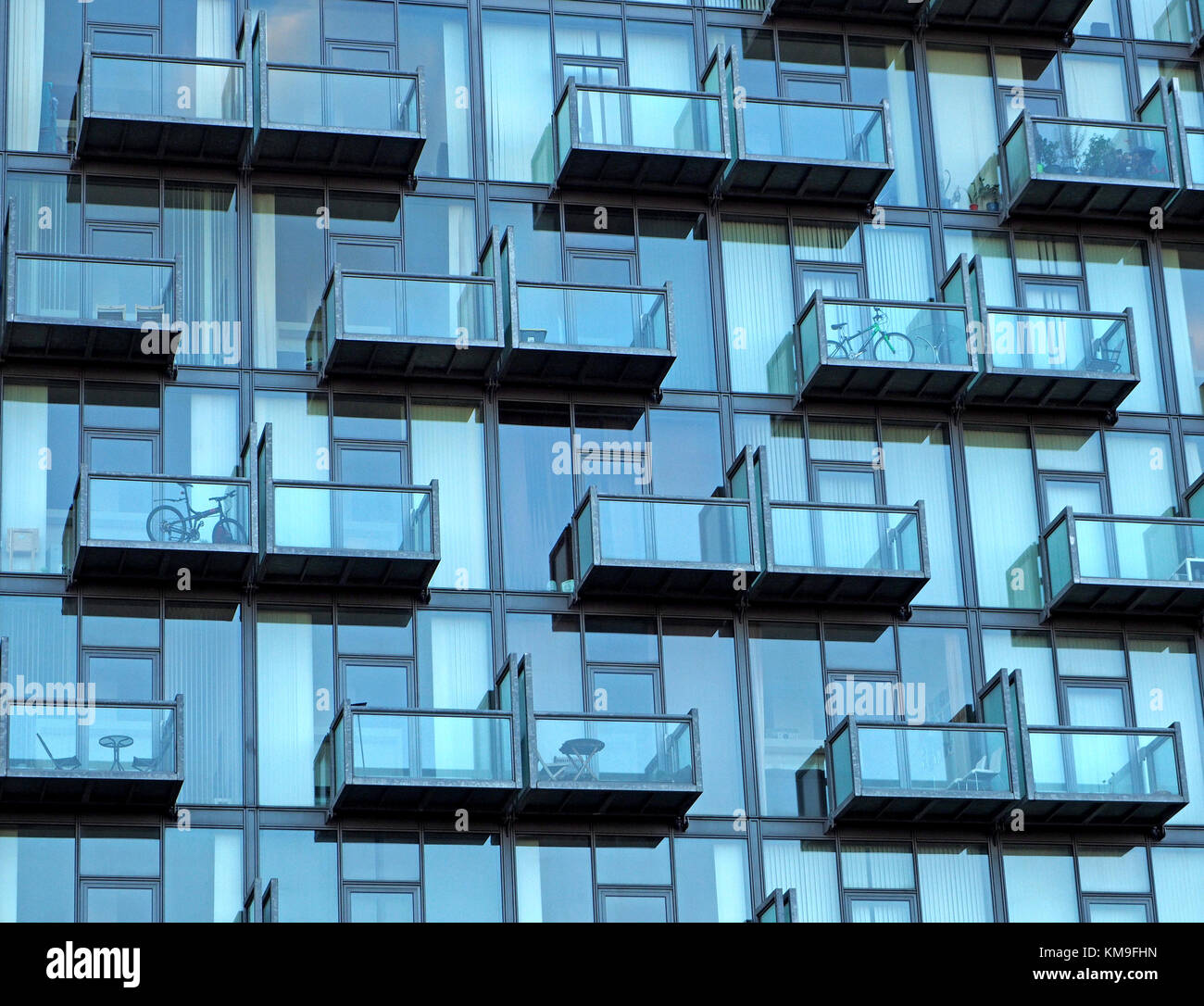 pattern created by grid of balconies with seating and bicycles on blue glazed frontage of new building at Salford - Stock Image