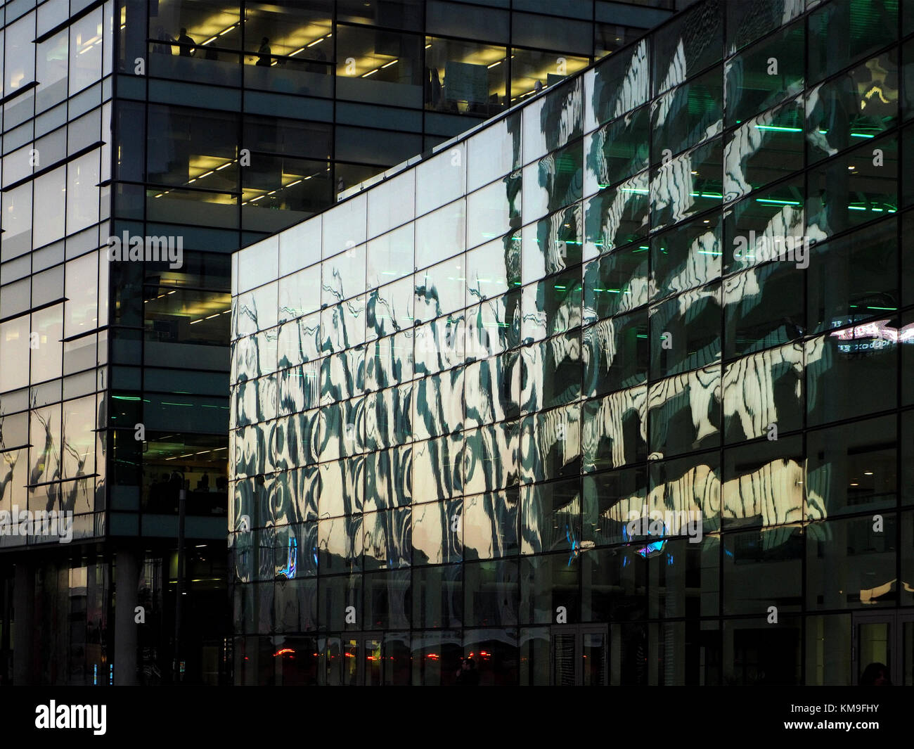 distorted reflections of the evening cityscape in new glazed buildings at Salford Quays, Manchester, UK as dusk - Stock Image