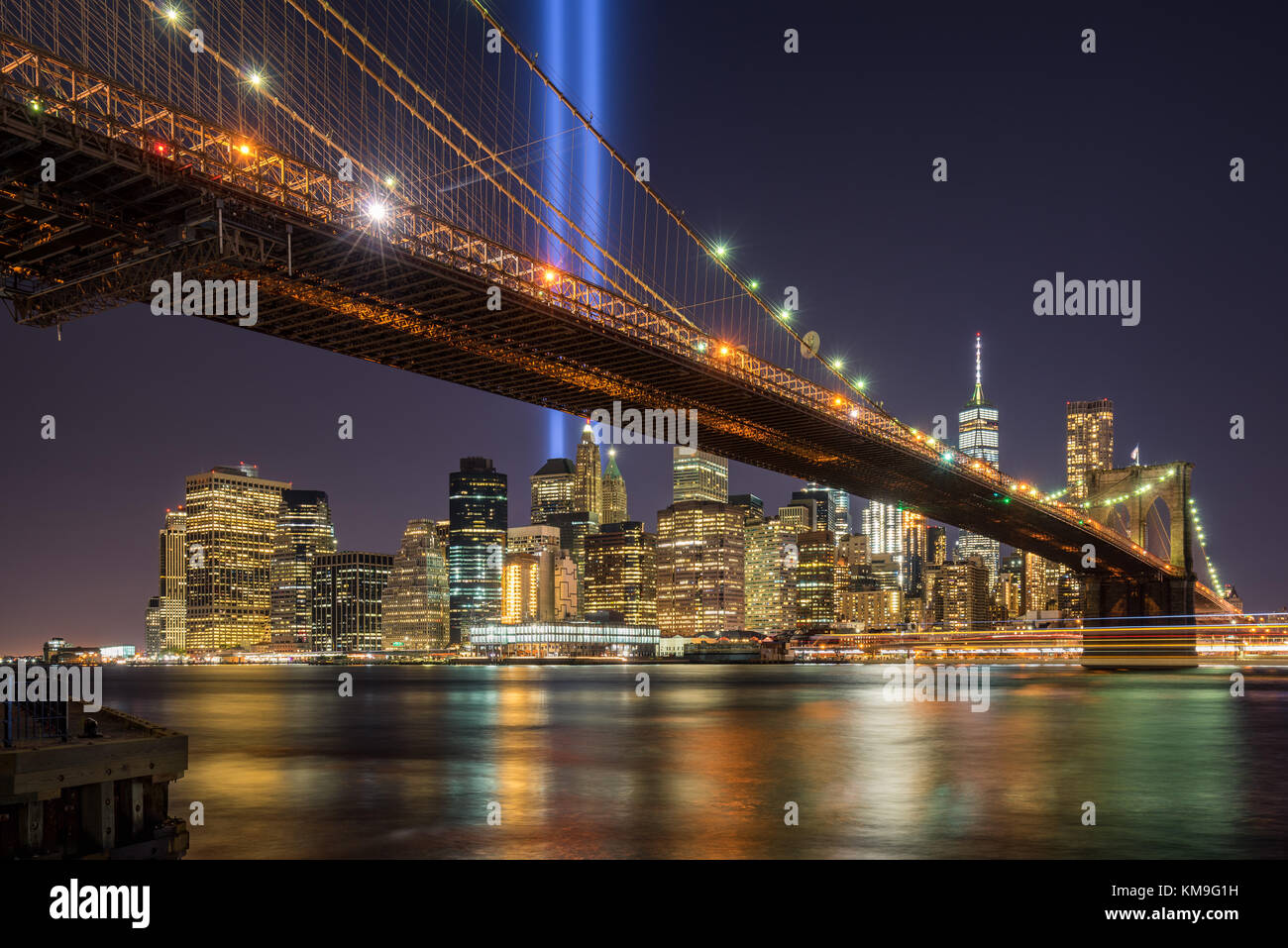 Tribute in Light with the Brooklyn Bridge and the skycrapers of Lower Manhattan. Financial District, New York City - Stock Image