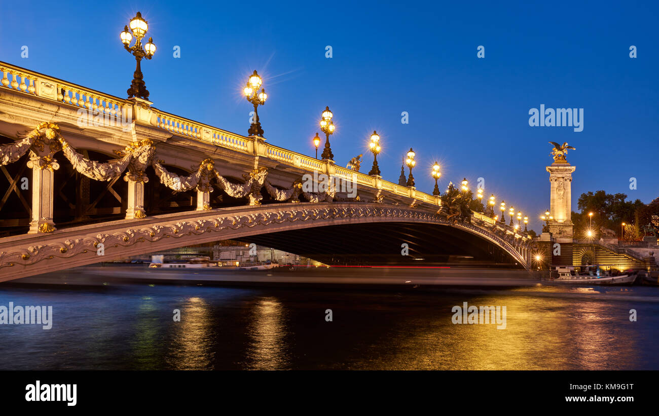 Panoramic view of the Pont Alexandre III bridge illuminated in evening with the Seine River. 8th Arrondissement, - Stock Image