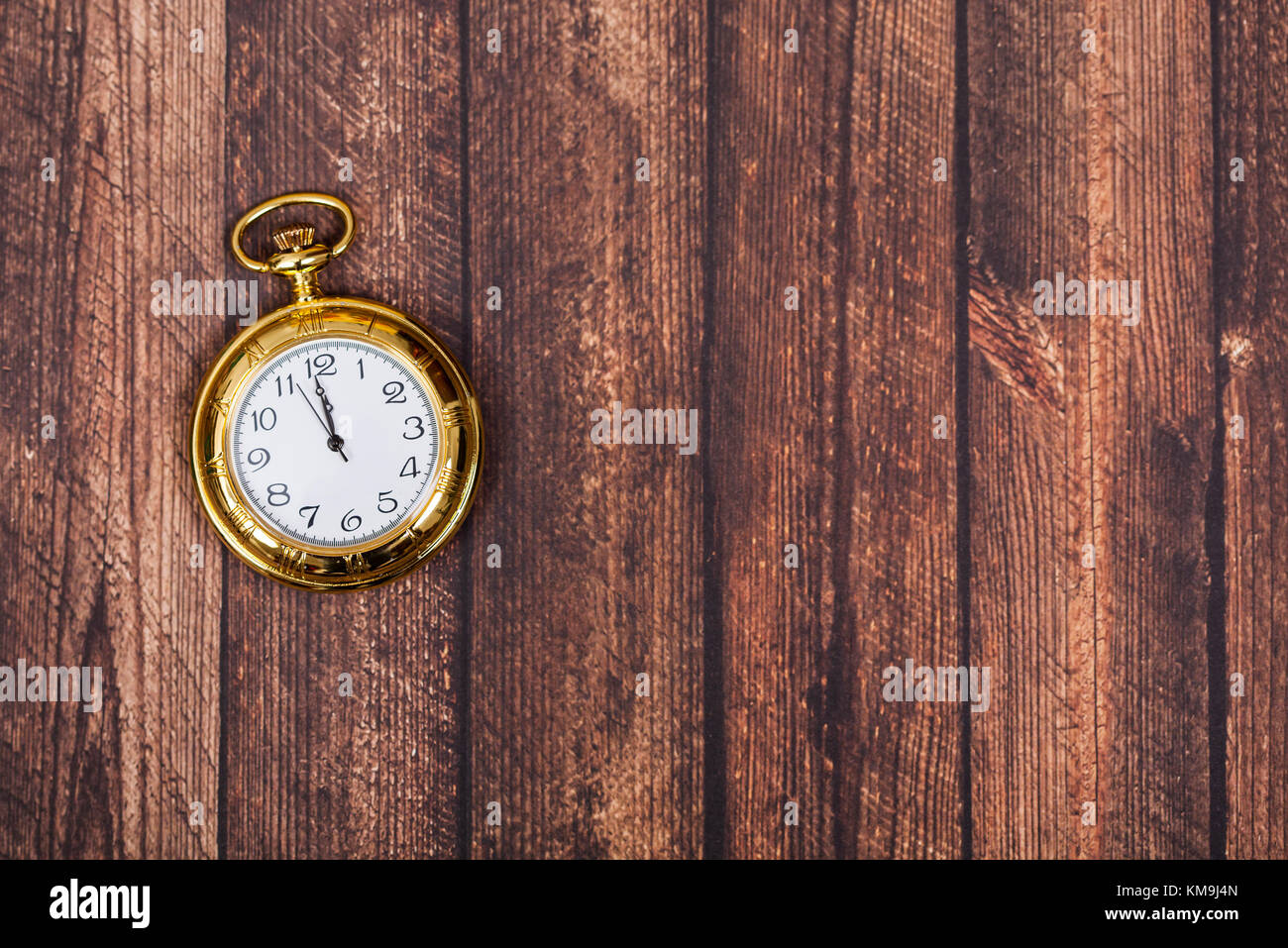 Vintage golden clock showing midnight, on wooden background Stock Photo
