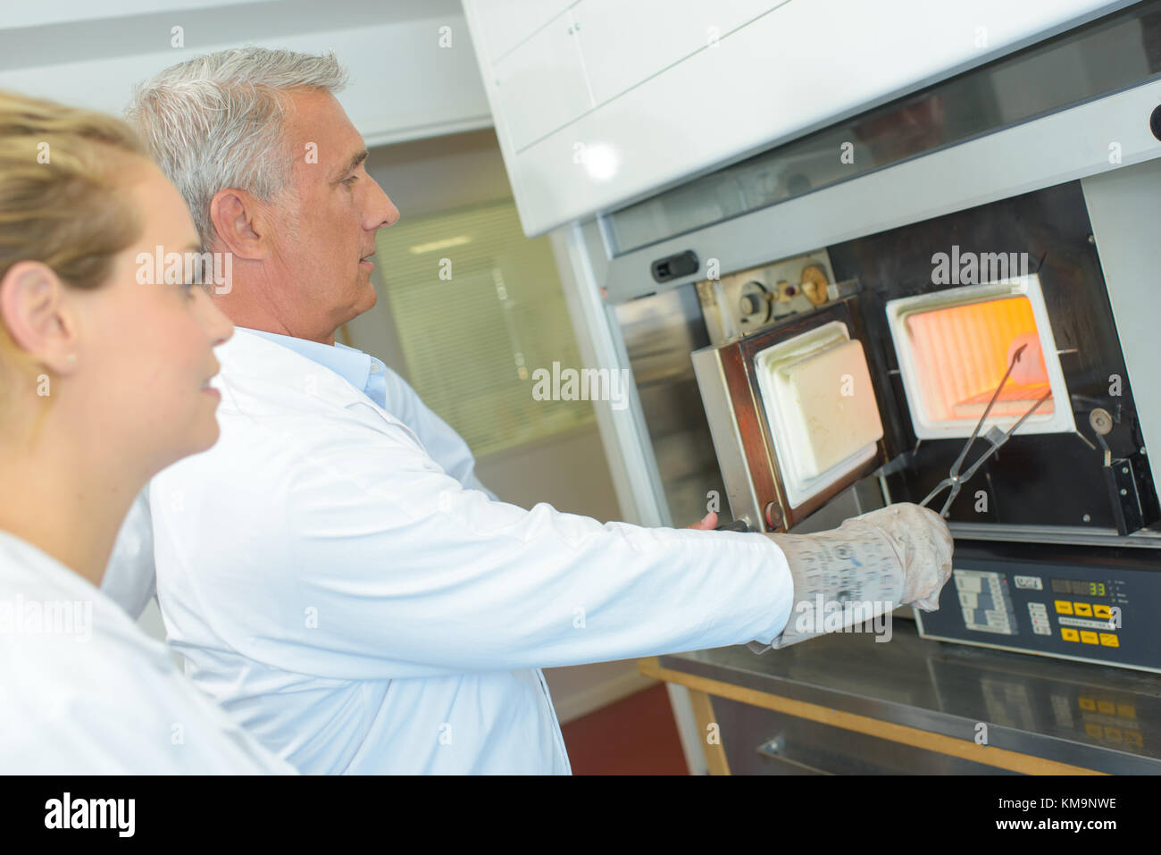 Man in white coat removing item from oven - Stock Image