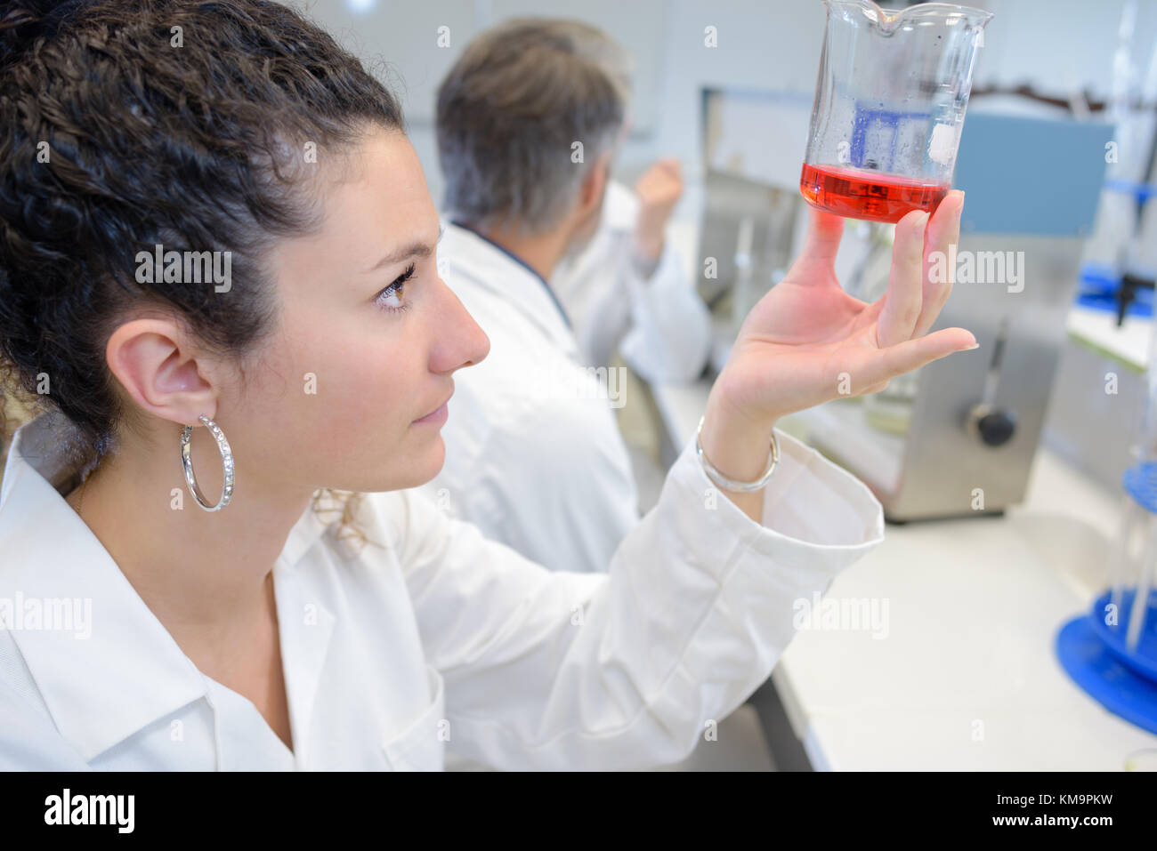 young laboratory student holding a flask with red liquid Stock Photo