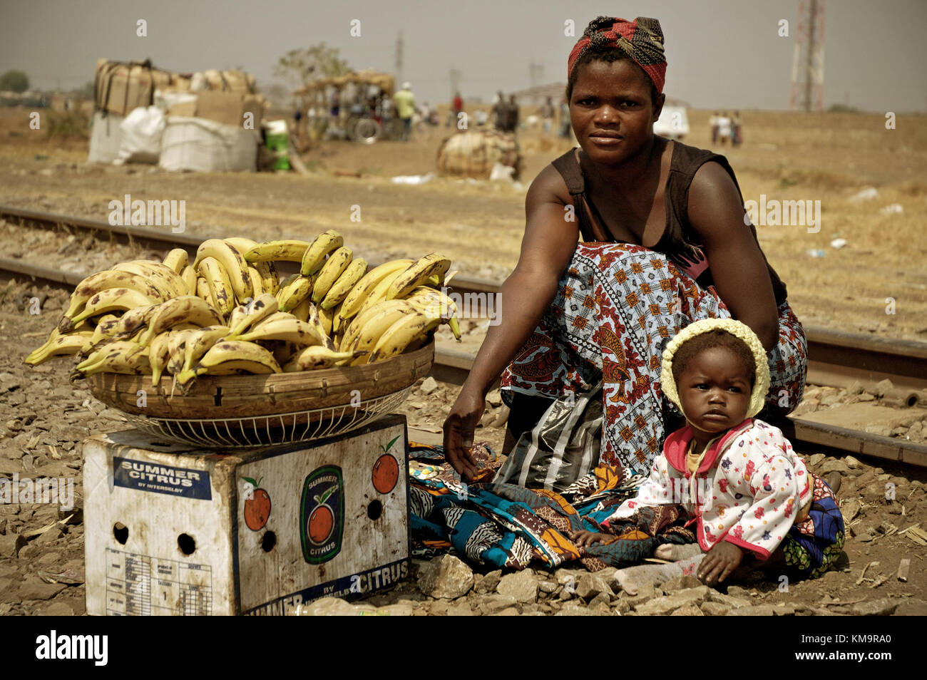 Mom selling bananas with her baby next to railway in Lusaka, the capital of Zambia Stock Photo