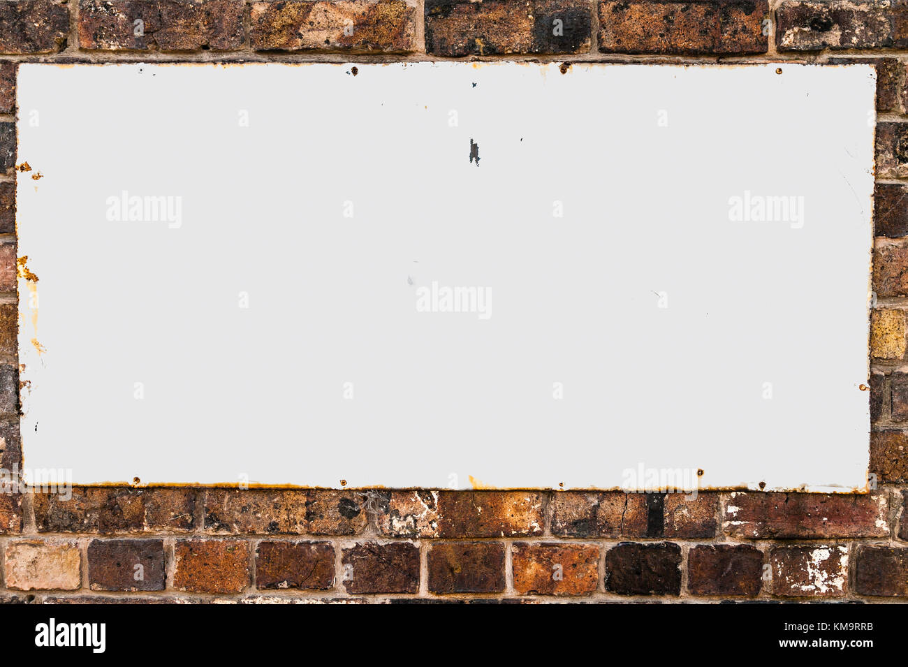 Vintage blank  white metal advertisement hoarding set in a oblong shape screwed to a weathered wall background. - Stock Image