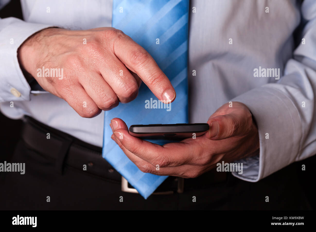 Man holding and touching screen or display with finger of a mobile phone, cell phone or smartphone. Male businessman - Stock Image