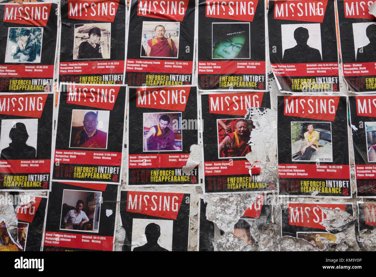 Posters on public wall giving information on Tibetans missing in their own country, presumably at the hands of China's - Stock Image
