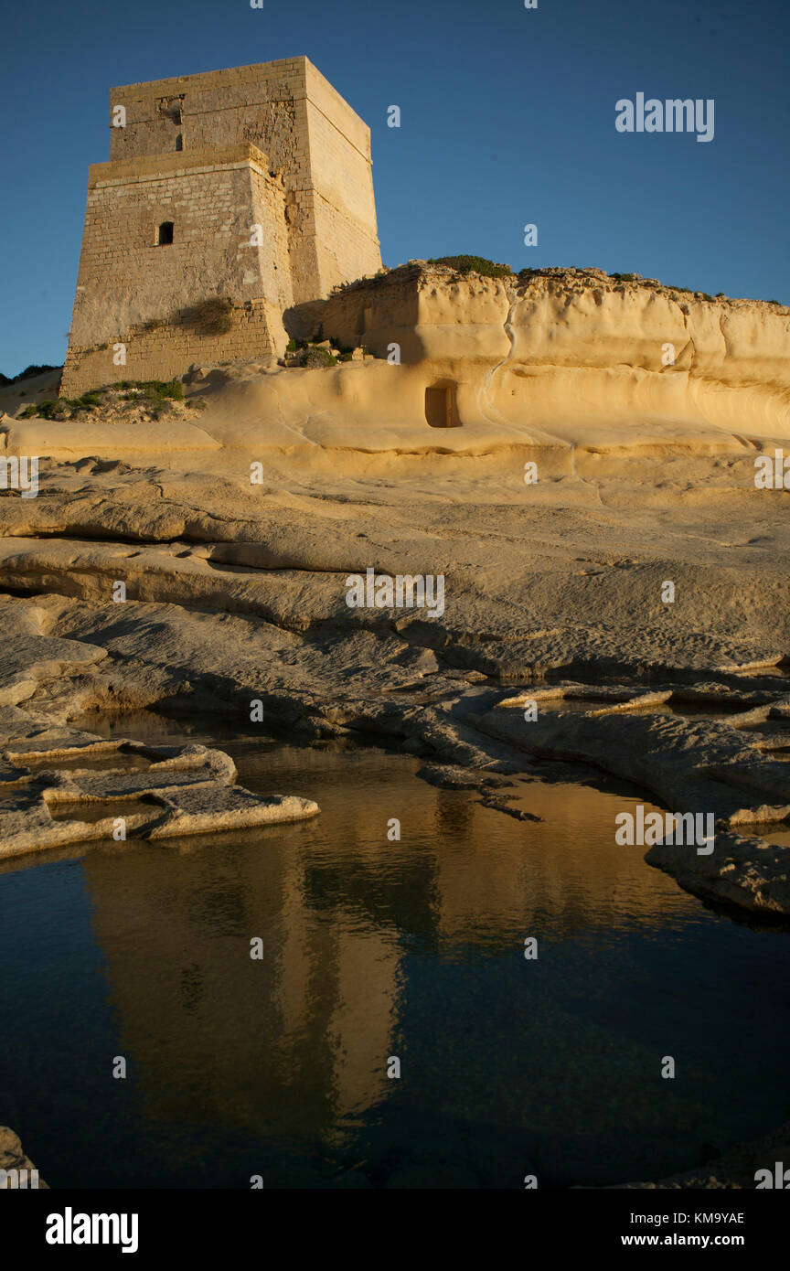 Xlendi Tower reflected in the salt pans below - Stock Image