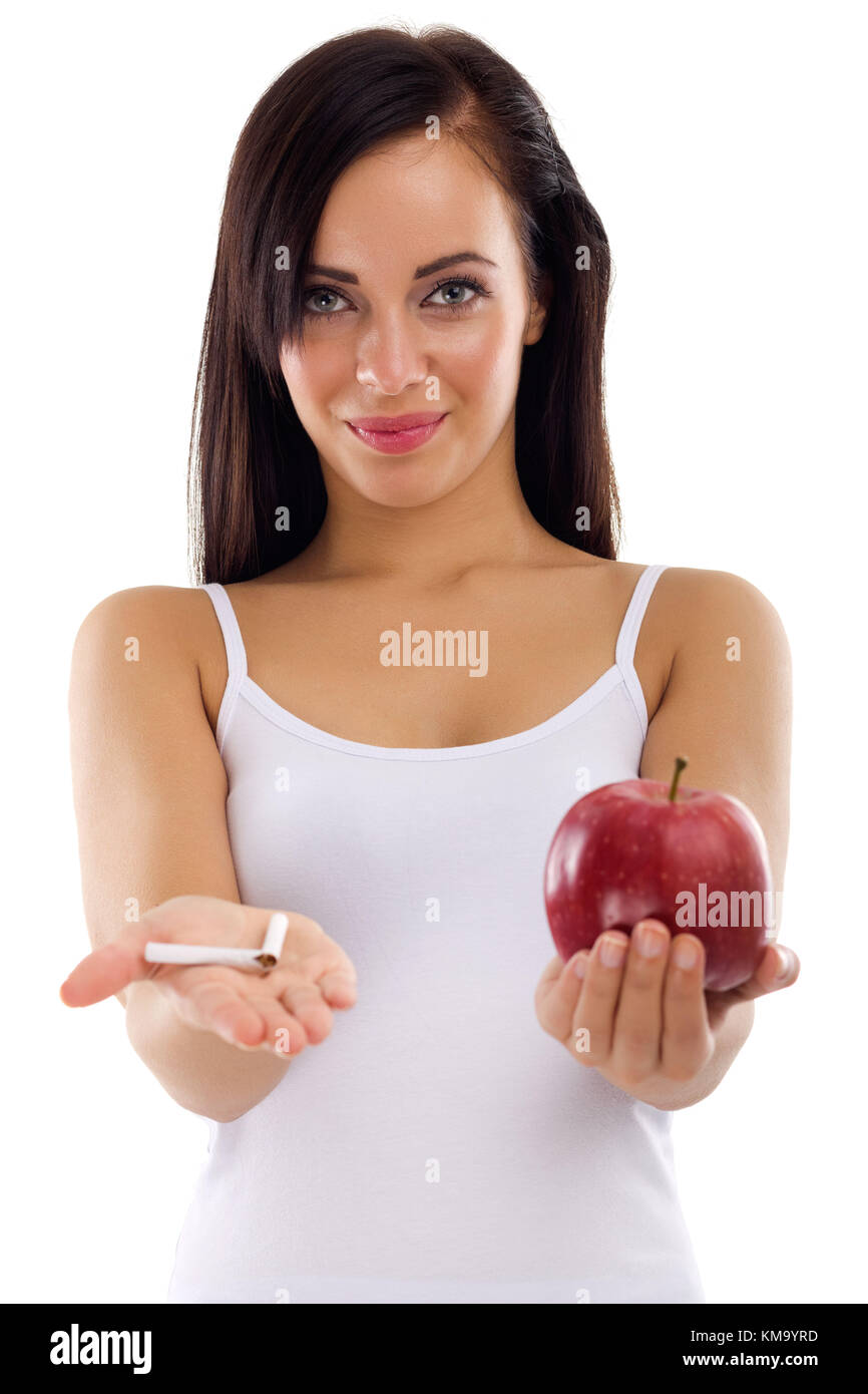 a young woman holding in one hand a broken cigarette in the other healthy apple cigar,stop smoking concept on white - Stock Image