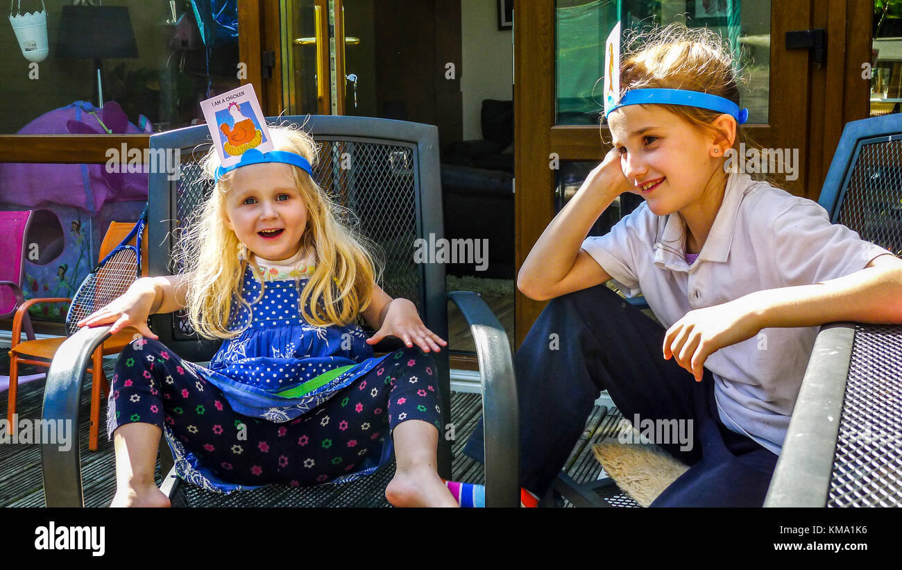Children family kids playing board game HedBanz sitting on deck chairs on the deck in the garden - Stock Image