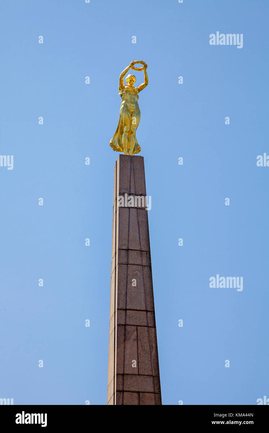 Stone obelisk with golden woman, Gelle Fra, memorial at Place de la Constitution, Luxembourg-city, Luxembourg, Europe - Stock Image