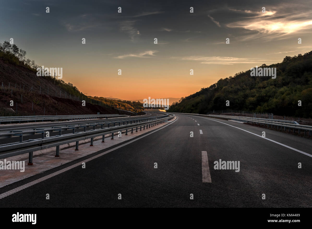 Empty Highway road with markings at sunset - Stock Image
