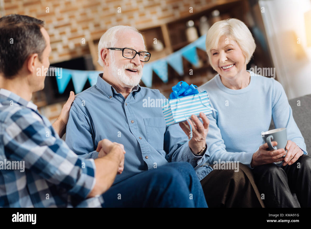 Elderly Man Looking At Birthday Present From His Family