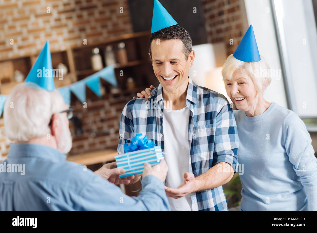 Elderly Man Giving A Birthday Gift To His Adult Son Stock Photo