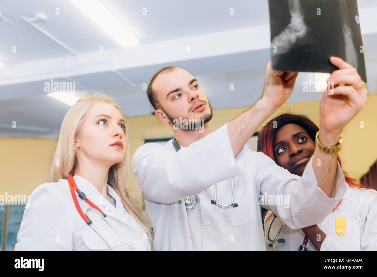 Multiracial team of young doctors looking at x-ray healthcare, medical and radiology concept - Stock Image