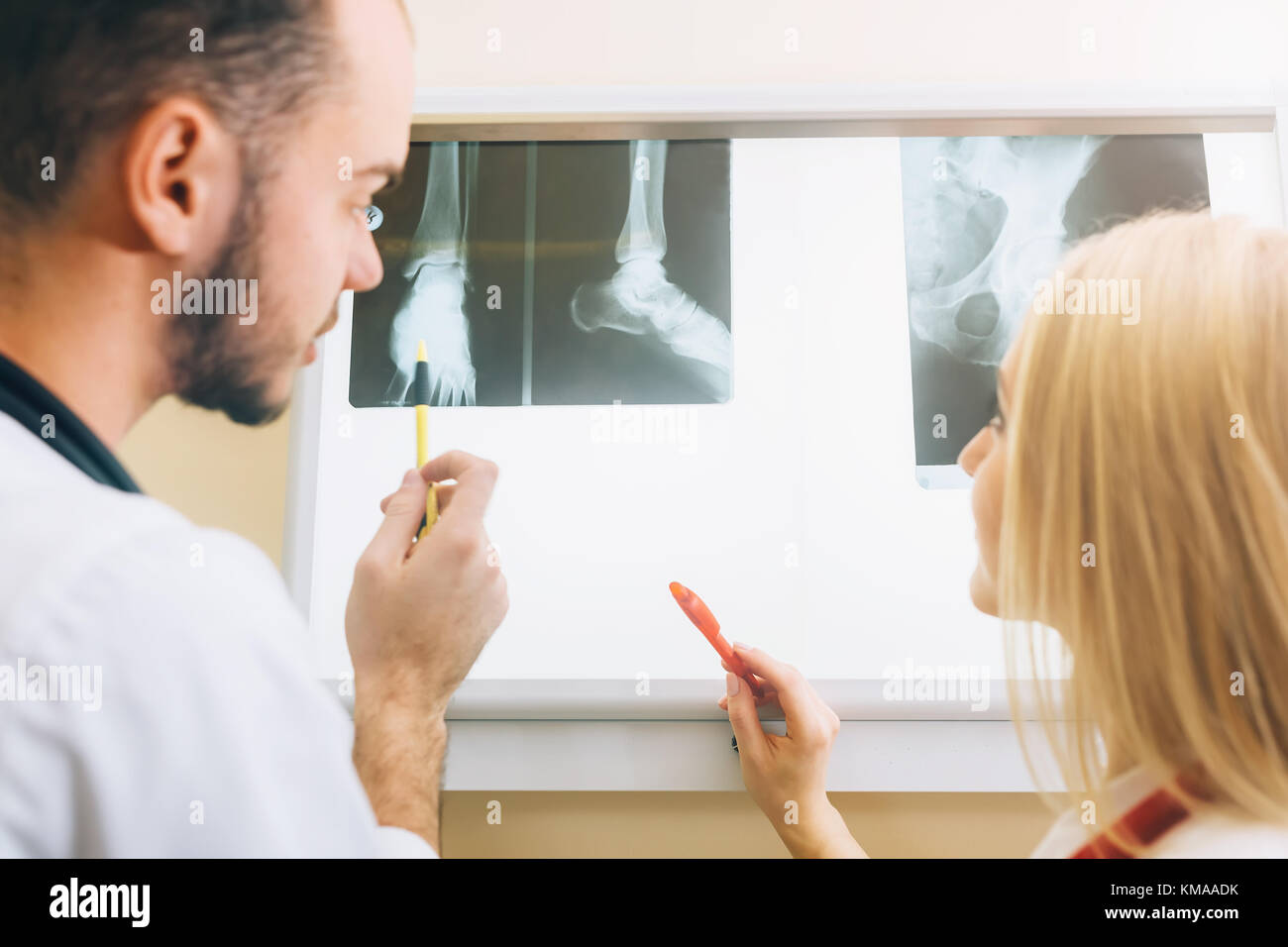 Two young doctors looking at x-ray healthcare, medical and radiology concept - Stock Image