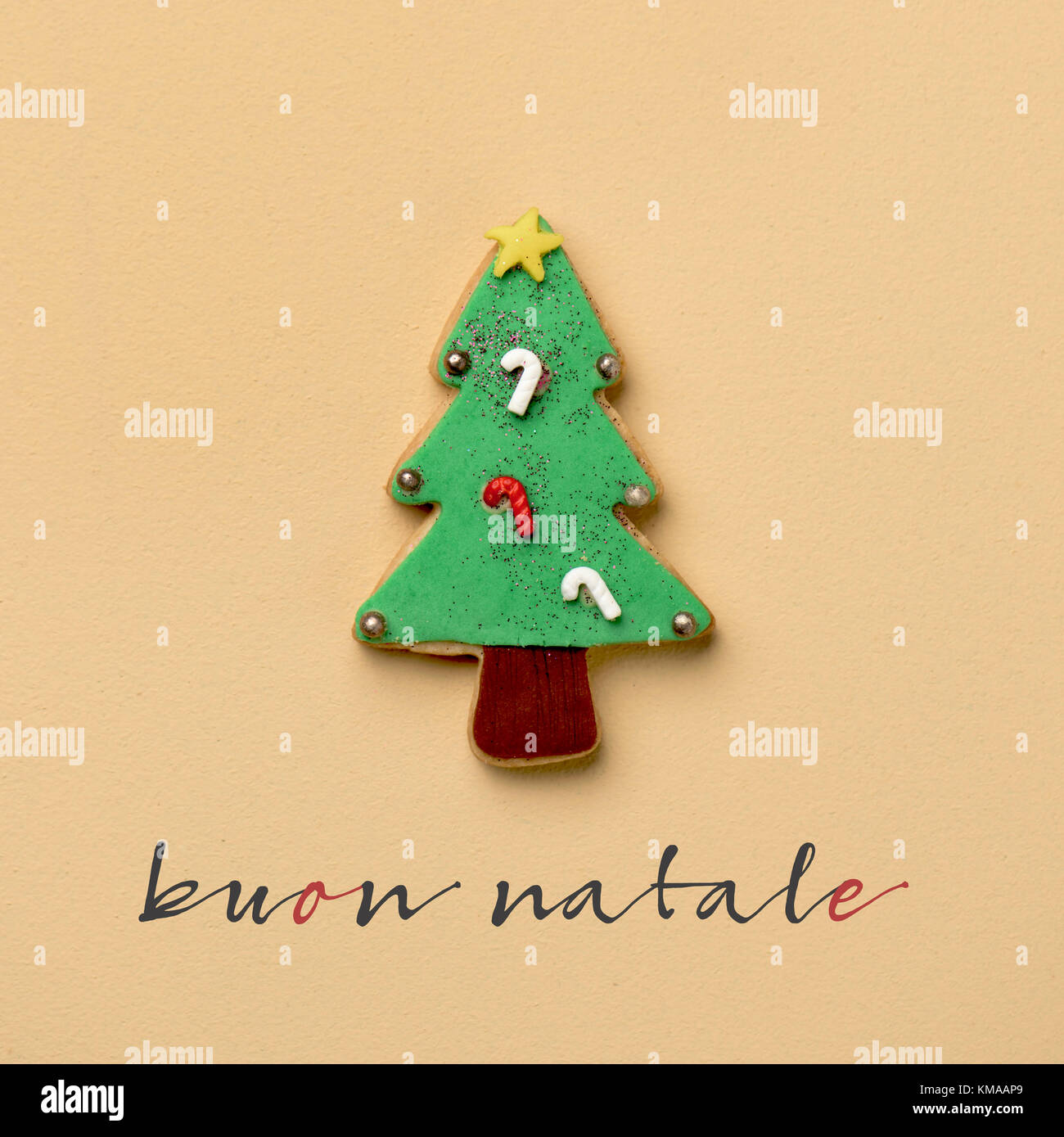 a coloroful cookie in the shape of a christmas tree and the text buon natale, merry christmas in italian, on an - Stock Image