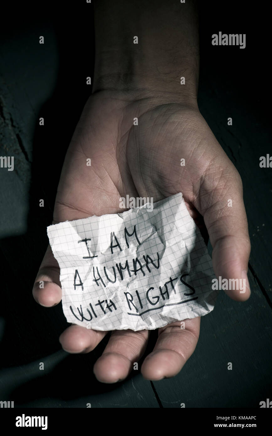 closeup of the hand of a young man with a piece of paper with the text I am a human with rights written in it - Stock Image