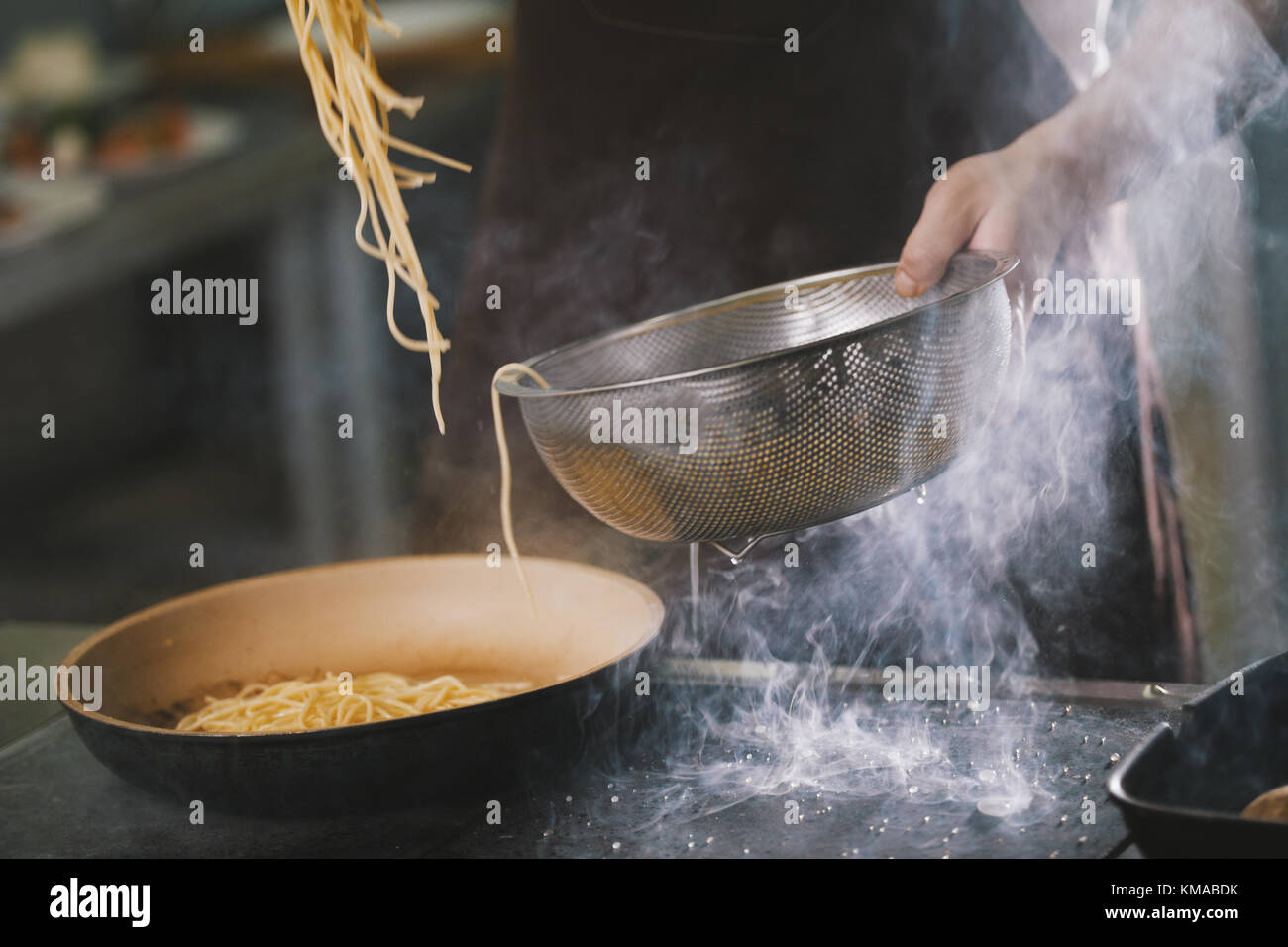 Cooking spaghetti in restaurant - Stock Image