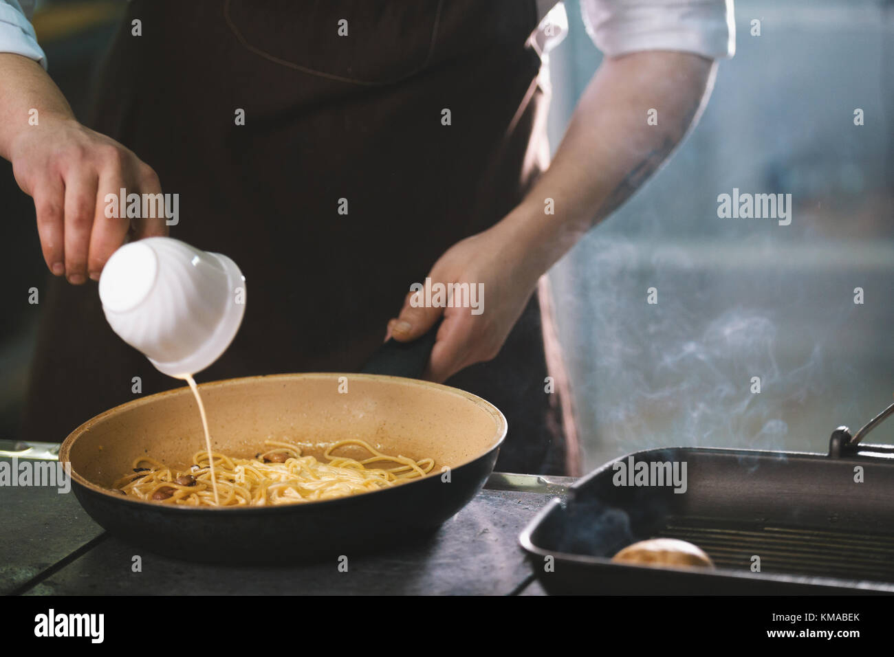 Chef is pouring the sauce into spaghetti - Stock Image