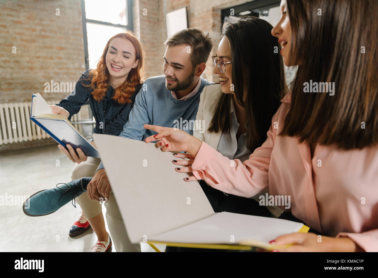 Interns laughing at their notes - Stock Image