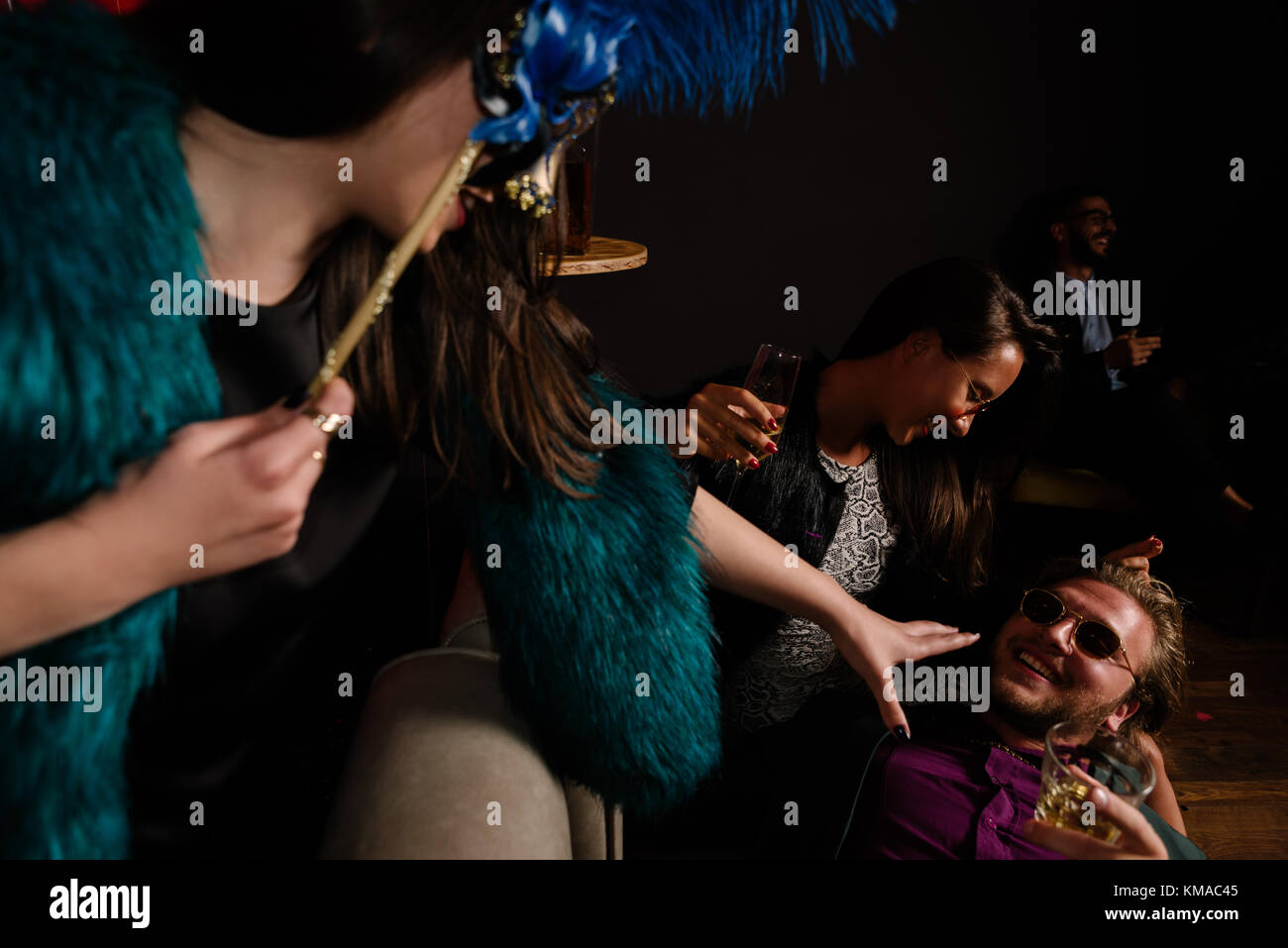Two girls fighting over Casanova's attention at a party - Stock Image