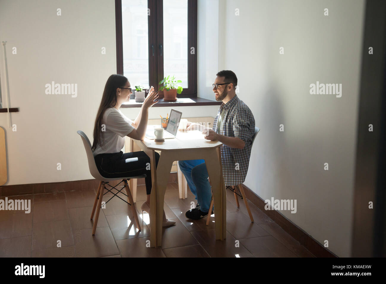 Coworkers sitting at meeting and discussing new concept in work. Two smiling millennial employees talking about - Stock Image