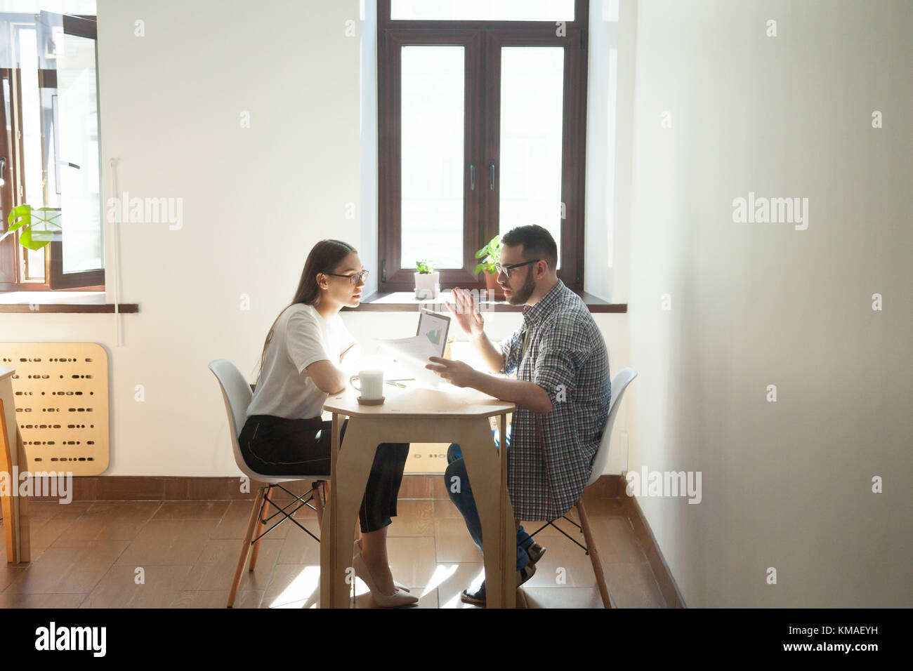 Businessman and businesswoman discussing working problems in office. Two millennial employees having business meeting - Stock Image