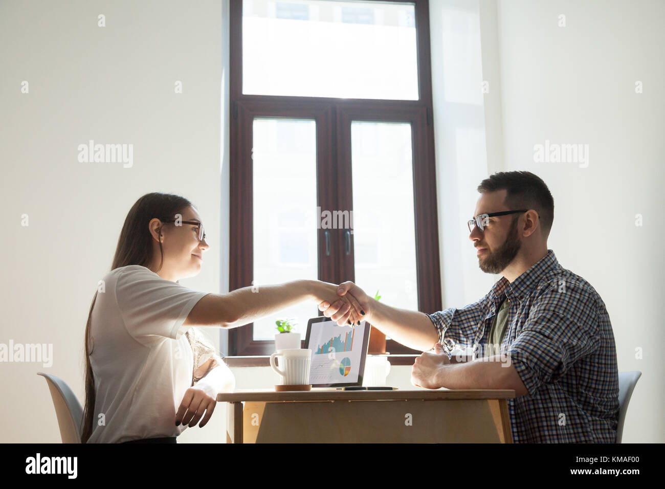 Friendly millennial businessman and businesswoman handshaking over office table after pleasant talk and business - Stock Image