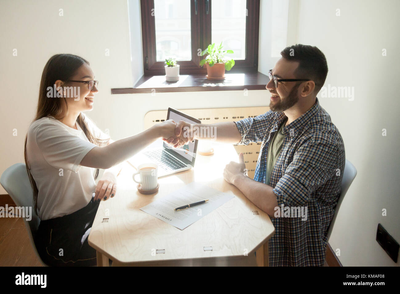 Friendly millennial businessman and businesswoman handshaking over office table after signing business contract. - Stock Image